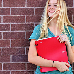 girl smiling holding binder notes school wall red green smile blonde hair hands portrait natural